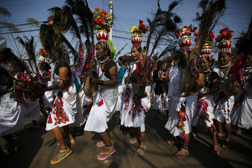 Tharu performers dressed in traditional attire participate in a parade marking an Elephant Festival event at Sauraha in Chitwan