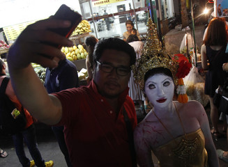 """A Thai woman dressed as a ghost poses for a """"selfie"""" with a man during Halloween night at famous backpacker paradise Kao San Road in Bangkok"""