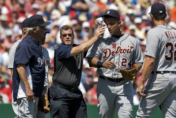Detroit Tigers manager Leyland and Kelly look on as  a trainer holds a towel to the bloodied face of third baseman Cabrera after a ground ball hit by Philadelphia Phillies' Pence bounced into his face during a spring training baseball game in Clearwater