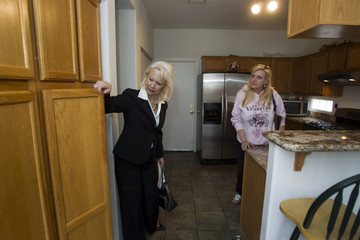 Reality Executives owner/broker Moore and realtor Riley look at kitchen cabinets of a home for sale in Henderson