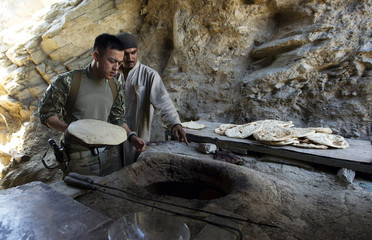 Sergeant Brian Baker, a medic connected to Bravo troop, 1st Squadron of the 75th Cavalry Regiment, 2nd Brigade of the 101st Airborne Division places bread into an oven in the kitchen of an Afghan National Police station near the city of Mara Wara in Afghan