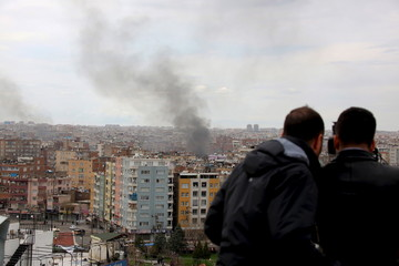Members of the local media make a video recording as smoke rises over Baglar district, where security operations and clashes between Turkish security forces and Kurdish militants take place, in the Kurdish-dominated southeastern city of Diyarbakir