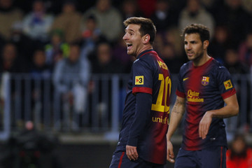 Barcelona's Messi smiles next to Fabregas during their Spanish First Division soccer match against Malaga in Malaga