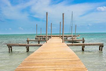 Wooden pier dock and ocean view at Caye Caulker Belize Caribbean.