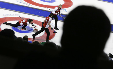 People are silhouetted as Team Canada skip Nedohin throws a rock against Manitoba during the Scotties Tournament of Hearts curling championship in Kingston