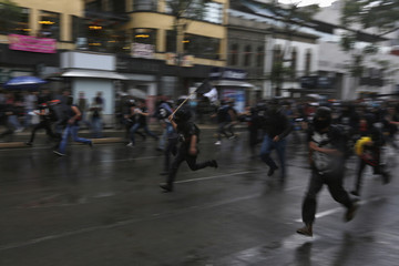 Demonstrators run during a march to mark May Day in Mexico City