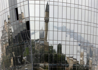 A mosque and the city waterfront are reflected in a new building in the Azeri capital Baku