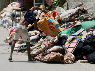 A man throws away clothes after they were caught in the floods in Wellampitiya