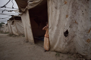 Khatija, a five-year-old flood victim, stands in front of her family tent while taking refuge at a camp for the internally displaced in Nowshera