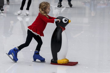 A child uses a penguin skating aid at the skating rink in Bryant Park during unseasonably warm weather on Christmas Eve in the Manhattan borough of New York