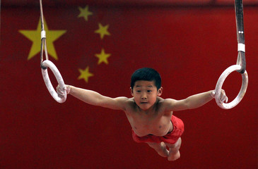 Young gymnast hangs from gymnastic rings in front of a Chinese national flag during a gymnastics class for children at the Shichahai Sports School in Beijing