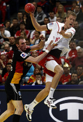 Glandorf of Germany challenges Markussen of Denmark during their Men's European Handball Championship main round match in Belgrade