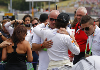 Philippe Bianchi, the father of late French Formula One driver Bianchi, is hugged by Formula 1 drivers before the Hungarian F1 Grand Prix at the Hungaroring circuit, near Budapest