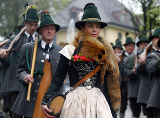 A Bavarian woman walks among mountain riflemen in traditional outfits during a parade in the southern village of Miesbach