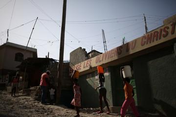 Women walk carrying buckets of water along a street of a slum in Port-au-Prince, Haiti