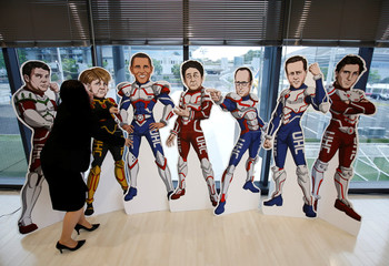 A staff member of the G7 Network of Health-related NGOs in Japan tries to adjust positions of cutout panels presenting the G7 countries' leaders as superheroes, at the G7 NGO center in Ise