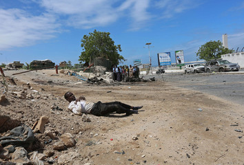 An injured member of staff of Somalia's Parliament lies on the ground during an attempted attack by Al Shabaab militia in Mogadishu
