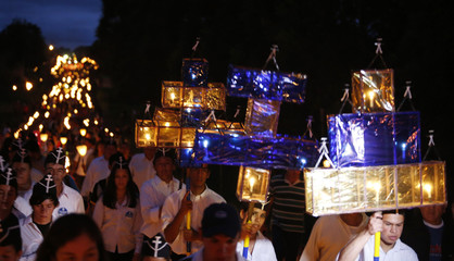 """Catholics, holding up lit candles,participate in a """"Via Crucis"""" (Way of the Cross) procession which commemorates the crucifixion of Jesus Christ, on Good Friday in Tanarandy, San Ignacio"""