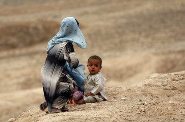 An Afghan girl plays with her younger brother in the  village of Ghazi Kalai