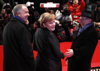 State Minister for Culture and Media Neumann, Berlinale festival director Kosslick and German Chancellor Merkel arrive at the red carpet for the movie 'Pina' at the 61st Berlinale International Film Festival in Berlin