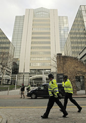Police pass offices of News International at Wapping in London