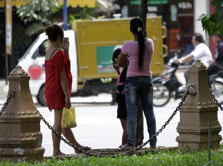 Cambodian sex workers wait for customers at a public park in Phnom Penh