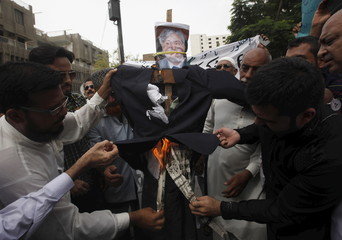Traders burn an effigy of Pakistan's Finance Minister Ishaq Dar, during a protest against the imposition of 0.6 per cent adjustable advance income tax on bank transactions, in Karachi