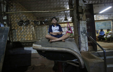 A boy sits on top of a mattress as he watches others perform during a Mallakhamb class at the Shree Samartha Vyayam Mandir in Mumbai
