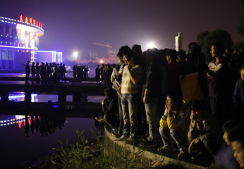People watch as riot police stand at the entrance of Zhili town government building after a protest in Huzhou city