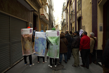 Revellers dressed as Euro banknotes stand on a street during the Carnival of Cadiz