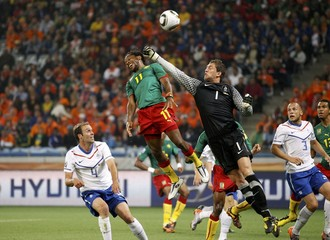 Netherlands' goalkeeper Stekelenburg tries to punch the ball away from Cameroon's Makoun during a World Cup soccer match at Green Point stadium in Cape Town