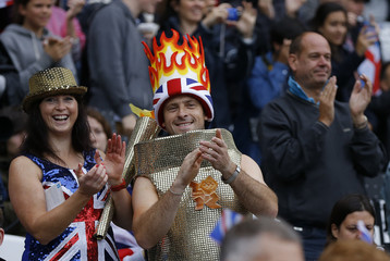 A spectator dressed as the Olympic flame applaudes while watching the morning's athletics events during the London 2012 Olympic Games at the Olympic Stadium
