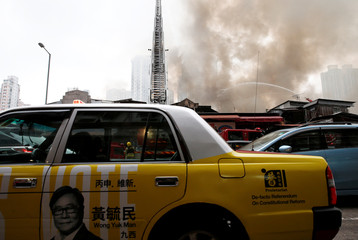 A taxi with a photo of Raymond Wong Yuk-man, candidate from Proletariat Political Institute drives past Yau Ma Tei Wholesale Fruit Market while smoke billows from the fire, in Hong Kong