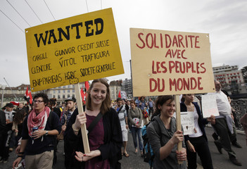 Protesters hold up placards during a demonstration against the FT Global Commodities Summit in Lausanne