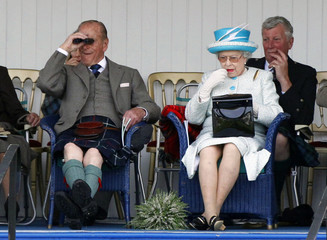 Britain's Queen Elizabeth applies lipstick as she sits next to her husband Prince Phillip during the Braemar Royal Highland Gathering in Scotland