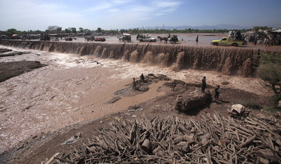 Residents use a bridge covered with floodwater in the Sarband area on the outskirts of Peshawar