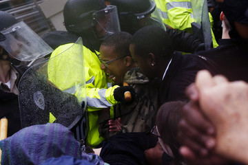 Ferguson police officers scuffle with protesters during a demonstration outside the police department in Ferguson, Missouri