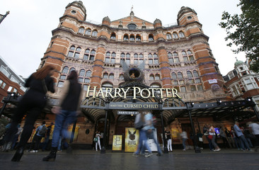 People walk past The Palace Theatre where the Harry Potter and The Cursed Child play is being staged, in London