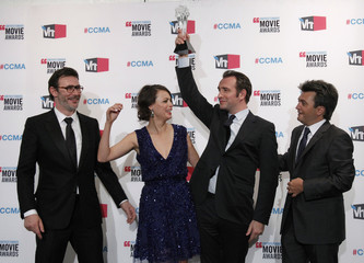 "Actor Dujardin raises the best picture award for ""The Artist"" as they celebrate their win backstage at the 2012 Critics' Choice Awards in Los Angeles"