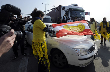 Slovak and Czech human rights activists drape Austrian national flag with picture of banana on it onto car during 15-minute blockade on Slovak-Austrian border crossing in Bratislava-Jarovce