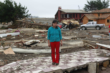 A girl stands on the floor of what was her home, destroyed by the waves generated by a major earthquake, near the epicenter in Pelluhue