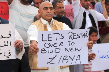 Supporters of Libya's unity government hold signs during a demonstration in Tripoli
