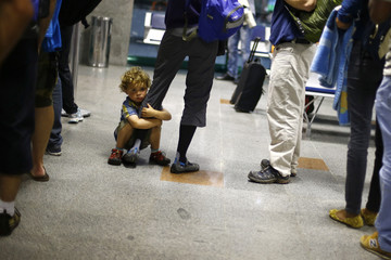 A child holds the leg of his mother at the Salvador de Bahia airport