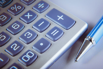 Pen and calculator on gray background