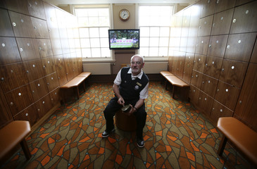 Golf attendant Ferguson poses for a photograph in the changing rooms that will be used for one of the Ryder Cup teams at the Gleneagles Hotel in Perthshire