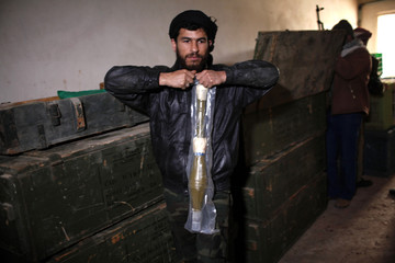 Free Syrian Army fighters check weapons which were seized at the army base at Hawa village, north Aleppo