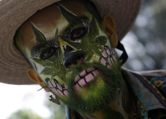 A demonstrator with his face painted takes part during a rally for the legalization of marijuana in Mexico City
