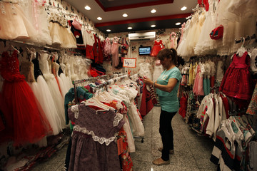 A shop owner waits for customers, ahead of the Eid al-Adha holiday in Baghdad's Karrada district