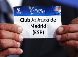 Champions League final ambassador Figo shows ballot paper carrying club name Atletico Madrid during the draw for the Champions League semi-finals matches at the UEFA in Nyon
