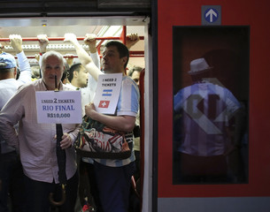 Soccer fans hold up signs to buy tickets for matches as they travel on a train towards the Corinthians arena at the Luz Station before the 2014 World Cup round of 16 soccer match between Argentina and Switzerland in Sao Paulo